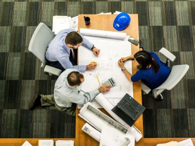 Three people sit at a table with blue prints. A blue hard hat can be seen.