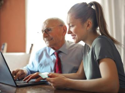 A young woman and an elderly man look at a laptop